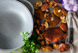 ingredients for cooking mushrooms on cutting board on grey stone background - 174255703