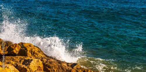 Papiers peints Bleu vert high cliff above the sea, summer sea background, many splashing waves and stone