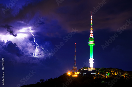 Seoul tower and Thunderstorm clouds with lightning at night Poster