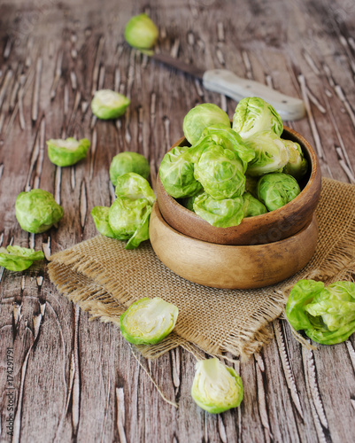 Poster Brussel Green raw Brussels sprouts in wooden bowl , selective focus