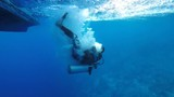 Underwater view of scuba diver backward roll entry into ocean from dive boat in Bunaken National Park, Sulawesi  - 174292391