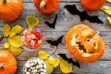 Carved smiling halloween pumpkin head among pumpkins on wooden background top view - 174323133