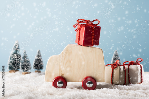 Poster Wooden toy car in winter landscape with gift boxes,  Merry Christmas concept.