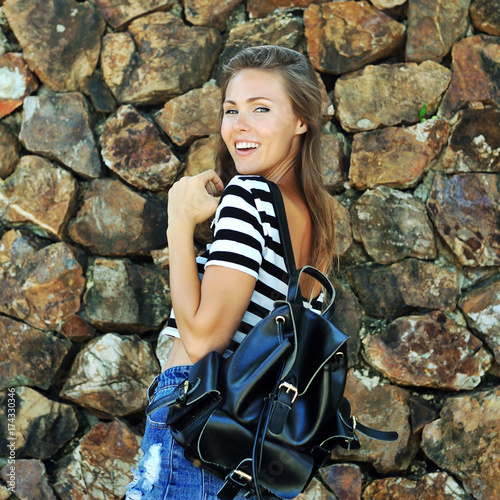 Happy girl with bag outdoor - portrait