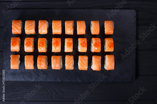Sushi rolls set with salmon set on black slate, flat lay, free space for text design