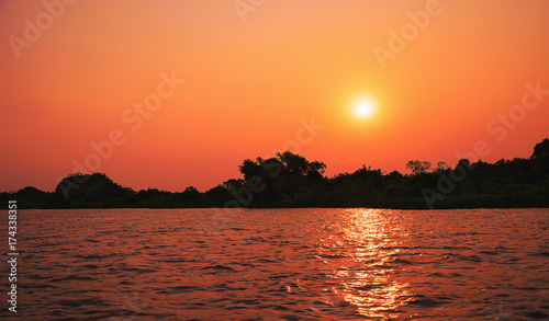 Papiers peints Orange eclat Amazing sunset at Paraguai river in Pantanal, Brazil. The river, the warm sun at sunset on a clear sky, water reflection of the light of sun and silhouette of trees on background.