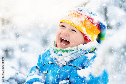 Papiers peints Kiev Baby playing with snow in winter. Child in snowy park.
