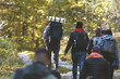A group of tourists walking in autumn forest