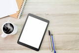 Blank white screen tablet computer with hot coffee cup, papers, notebook and pens on wooden desk - 174398769