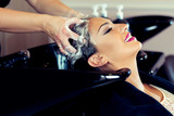 Beautiful young woman with hairdresser washing head at hair salon - 174406123