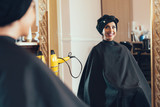 Woman in a beauty salon looks at her reflection in the mirror - 174406158