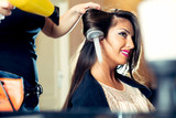 Hairdresser dries hair with a hairdryer in beauty salon - 174406517