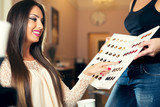 Happy young woman with hairdresser choosing hair color from palette samples at salon - 174406596