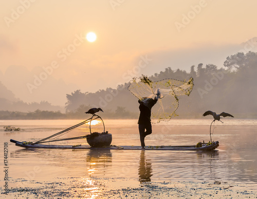 Staande foto Guilin Cormorant fisherman throws a net with ancient traditional chinese bamboo boats at sunrise - Xingping, China