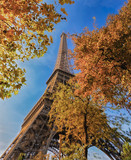Color image of the Eiffel tower in Paris, France, Europe, on a sunny autumn day with blue sky and colorful leaves