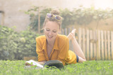 Cheerful girl reading a book and laughing - 174458791