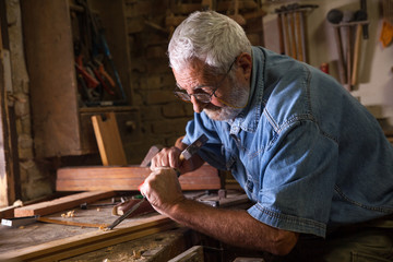 Senior man carpenter working with chisel in his old fashion workshop.
