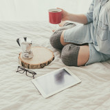 Closeup of young woman drinking coffee while sitting on bed - 174479985