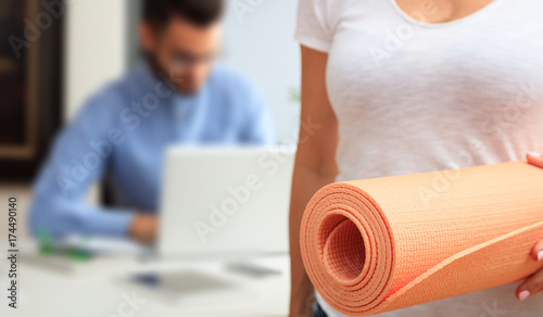 Poster Woman with an exercise mat in an office background
