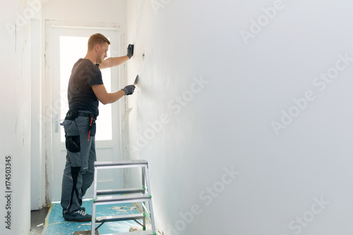 home interior construction - worker repairing wall