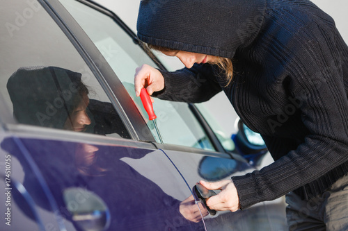 Thieft man holding screwdriver breaking into car