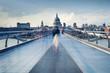 People walking over Millennium bridge at dusk.