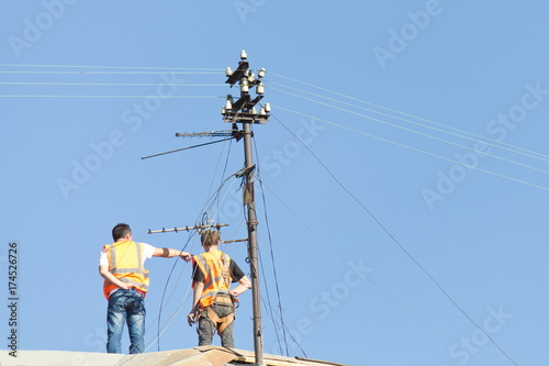 steeplejacks on the roof of the building which is under repair