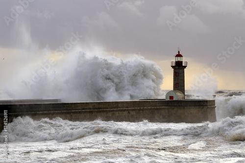 Fotobehang Vuurtoren Big wave against lighthouse at sunset