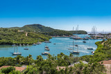 Small caribbean cove with sail boats and small motor boats - 174528333
