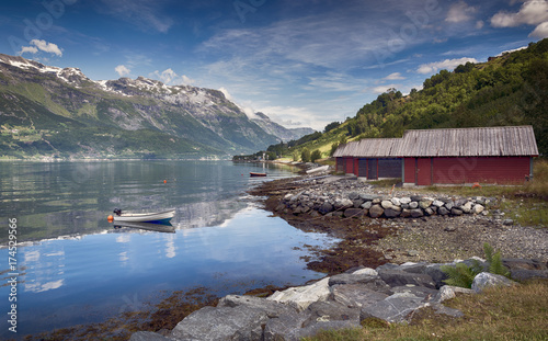 red houses and a boat in the fjord in norway - 174529566