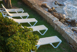 White sunbeds on the green grass at sunset time - 174530765