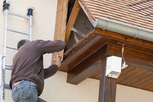 homme renove le bardage en bois