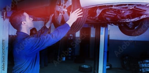 Poster Auto mechanic examining car tire