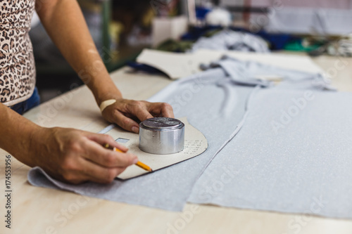Closeup view if woman hands patterning and tailoring. Tailor woman working in his tailor shop,