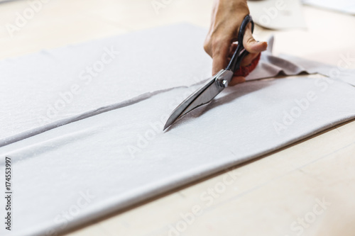 Woman hands of seamstress cutting a grey fabric with scissors. Tailor working in her shop cutting a roll of grey fabric