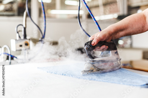 Professional ironing in dry cleaner detail of iron and hands. Presser in sewing clothes pressed