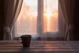 Cup of black coffee or tea in front of the window on the wooden table. Copy space. Romance sunset. - 174570506
