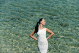 Girl standing in sea water - 174584913