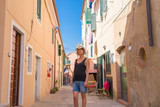 Italian summer holidays: woman standing alone in a colorful alley narrow street in an old village in Sicily, Italy