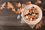 Autumn oatmeal with apples, cranberries, seed and nuts, top view on wood with fall leaves - 174634552