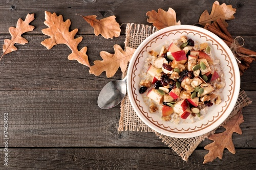 Tuinposter Herfst Autumn oatmeal with apples, cranberries, seed and nuts, top view on wood with fall leaves