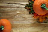 Pumpkins and autumn leaves on wooden background - 174638509