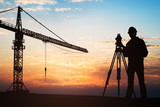 Surveyor Standing With Equipment At Construction Site - 174668342