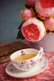 A cup of tea, old books and peonies on a table - 174687583