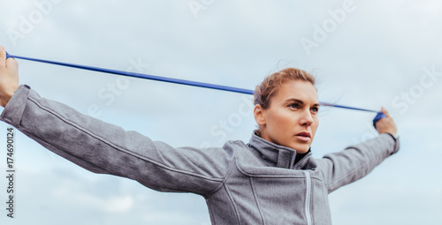 Young and fit woman exercising with resistance band