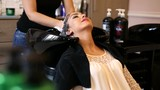 Beautiful young woman with hairdresser washing head at hair salon - 174705522