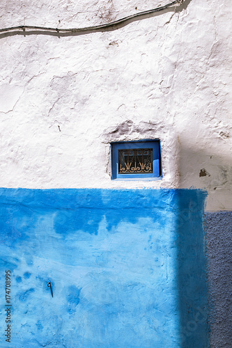 Fotobehang Marokko una pequeña ventana pintada en azul sobre una pared blanca y azul en Chaouen,Marruecos