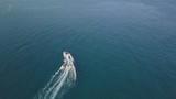 Motor Boat tows inflatable circle with vacationers at sea - 174713161