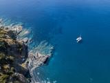 Vista aerea di una scogliera a picco sul mare e di un catamarano ormeggiato, barca. Penisola di Cap Corse, Corsica. Tratto di costa. Francia