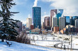 View of Downtown Calgary Covered in Snow on a Freezing Winter Morning. A Snow Covered Wooden Bench is Visible in Foreground.